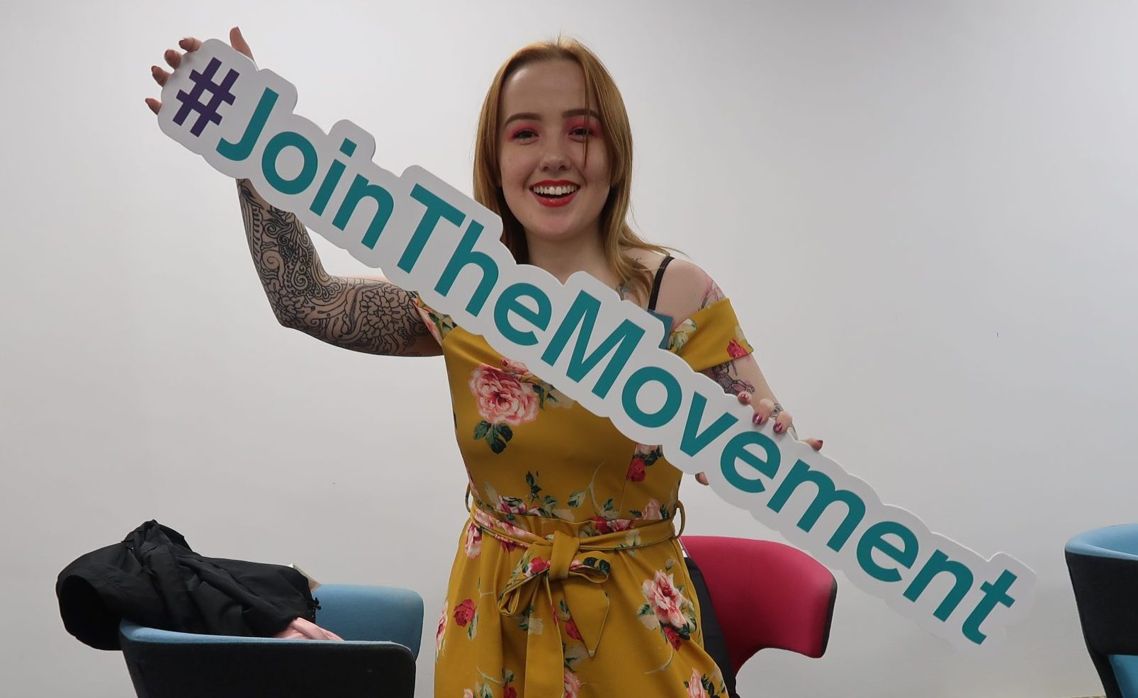 Young woman holding a sign that says #JoinTheMovement