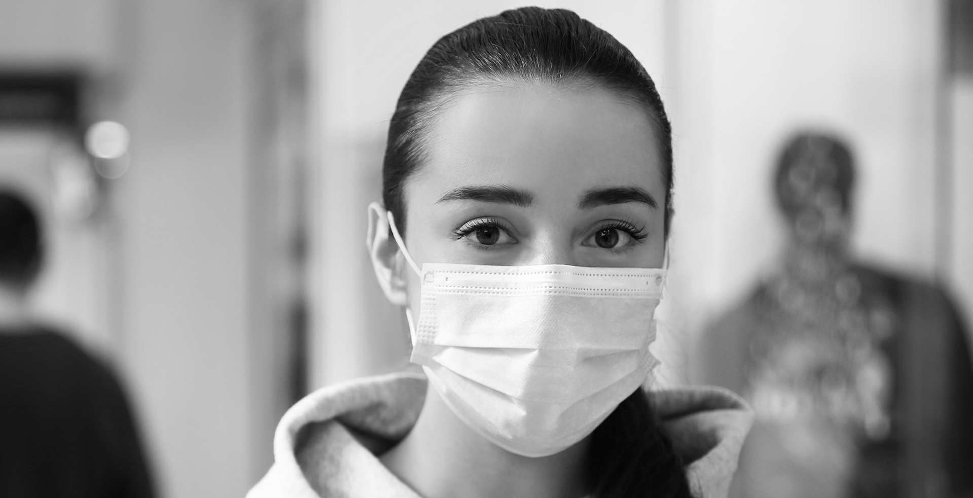 A women wearing a face mask looks into the camera