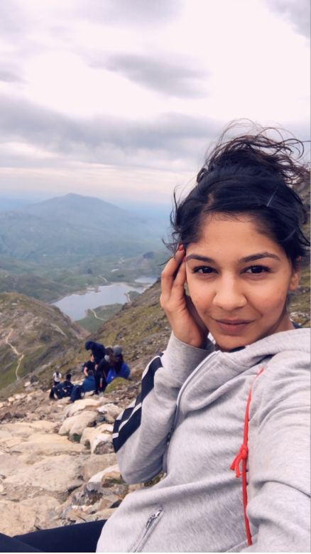 Shanice takes a selfie at the top of Mount Snowdon. She is sitting on a rock in a gre zip up hoodie.