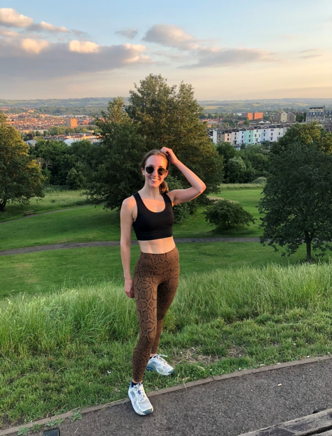 Cyan stands in running clothes at the top of a grassy hill. You can see a built up city behind her. She is wearing sunglasses and the sun is setting into the evening.
